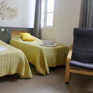 Chambre d'hôtel twin à louer dans Bordeaux centre ville composée de 2 lits, 1 fauteuil, 1 bureau, 1 armoire et 1 salle de bain