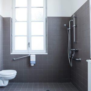 Salle de bain de la chambre avec une douche adaptées pour les personnes handicapées